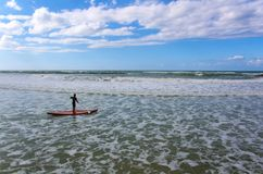 Seascape with a surfer on a paddleboard royalty free stock images