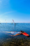 Seascape with surfers and windsurfers Stock Photos