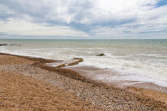 Seascape in Sussex with nobody on the beach. View of pebble beach with stong waves and a cloudy sky.  Taken on a trip to Eastbourne in early summer Royalty Free Stock Photos