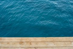 Seascape texture from above. Top view deep blue sea and wooden floor of a pier Royalty Free Stock Photos