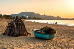 Seascape tropical com Sandy Beach, Coracle, Woodpile, pessoa, ondas, montanhas no nascer do sol imagem de stock