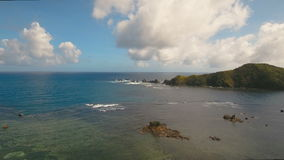 Seascape with tropical island, beach, rocks and waves. Catanduanes, Philippines. Aerial view coast of the tropical island with the mountains and the rainforest stock video
