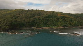 Seascape with tropical island, beach, rocks and waves. Catanduanes, Philippines. The coast of the tropical island with the mountains and the rainforest on a stock video footage