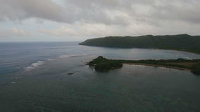 Seascape with tropical island, beach, rocks and waves. Catanduanes, Philippines. stock video