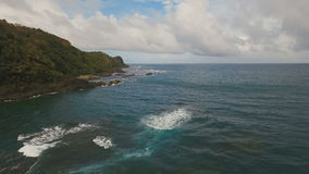 Seascape with tropical island, beach, rocks and waves. Catanduanes, Philippines. The coast of the tropical island with the mountains and the rainforest on a stock footage