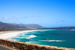 Seascape, turquoise ocean water waves, blue sky, white sand lonely beach panorama Chapmans Peak Drive road, South Africa coast t stock photo