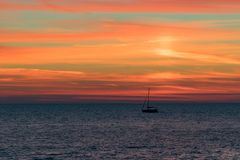 Seascape with a vibrant sunset over a calm sea and a floating boat. Royalty Free Stock Image