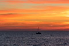 Seascape with a vibrant sunset over a calm sea and a floating boat. Stock Image