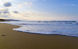 Seascape. A view from the beach, showing the waves, sand, sky and clouds Stock Image