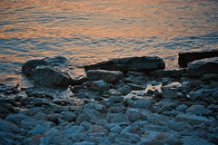Seascape view. Rocky beach in evening. Pebble shore. Tinted photo Stock Photo
