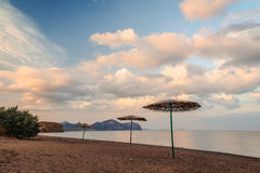 Seascape view of the sandy beach. With three umbrellas and cloudy sky Stock Photo