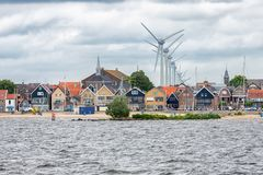 Seascape village Urk with wind turbines raising above the houses. Seascape Dutch fishing village Urk with big wind turbines raising above the skyline of the royalty free stock images