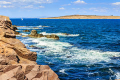 Seascape with waves crashing the shore and island Royalty Free Stock Photography