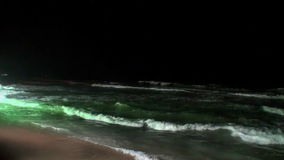 Seascape and waves glow at night in Maldives. stock video footage