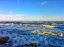 Seascape with waves, splashes and blue sky Stock Photography