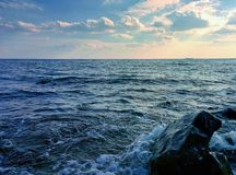 Seascape with waves and splashes. Seascape with waves, splashes, clouds and rock Royalty Free Stock Photos