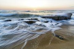 Seascape of waves splashing against rock Stock Images