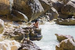 Seascape with wet brunette girl in black swimsuit. Secluded place of wild rocky coast in summer day Stock Image