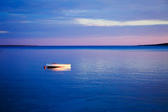 Seascape with White Boat in Blue Sea at Sunset Royalty Free Stock Photo