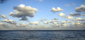 Seascape with white Clouds. A blue sea with a sky full of white clouds Stock Images