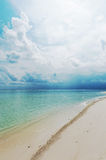 Seascape with white sand on the beach and blue sky with clouds Stock Photos
