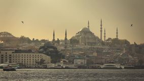 Seascape with wiews of old historical buildings of Istanbul Turkey with Suleymaniye mosque in a sunbeams at sunset. Slow stock video