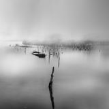 Seascape with wrecked boat and pillars in the mist stock photos