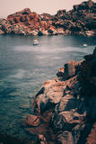 Seascape with yachts. Transparent sea water, yachts and huge red stones royalty free stock images