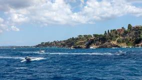 Seascape z szybkościowymi łodziami krzyżuje błękitnego morze śródziemnomorskie w tle niewygładzony skalisty brzeg Ludzie cieszą s zdjęcie stock