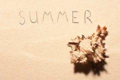 Seashell и литерность лета нарисованная на песке Стоковое Изображение