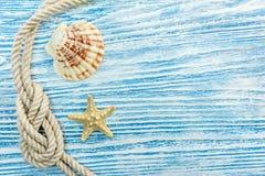 Seashell, морская звёзда, морская веревочка на голубых деревянных поцарапанных досках Стоковое фото RF