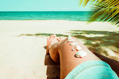 Seashell на загоренной ноге девушки на тропическом пляже в лете Стоковые Изображения