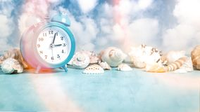 Seashell border and an alarm clock on a blue table against a blue sky with clouds - summer holidays and vacation time concept,. Copy space, place for text royalty free stock image