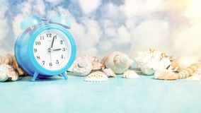 Seashell border and an alarm clock on a blue table against a blue sky with clouds - summer holidays and vacation time concept,. Copy space, place for text stock photo