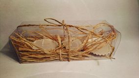 Seashell candles in a clear box with straw. Seashell with candles then packed in a clear box with straw Royalty Free Stock Photo