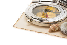 Seashell and compass on old paper. At white background Royalty Free Stock Photo