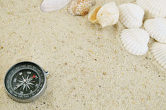 Seashell with compass on sand Royalty Free Stock Photos