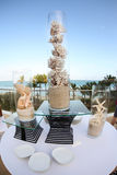 Seashell decorations. Unusual seashell decorations in tall glass tubes with sand on patio dining table with sea in background Stock Photography