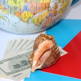 Seashell on dollars background. Nearby is a globe stock photo