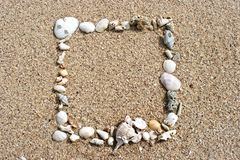 Seashell frame on sand background Royalty Free Stock Image
