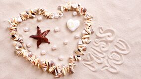 Seashell heart in sand Stock Photo