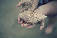 Seashell Holding des kleinen Mädchens lizenzfreie stockfotos