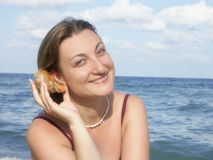 Seashell murmuring. Young woman at the beach putting seashell up to her ear and listening its murmur Royalty Free Stock Photos