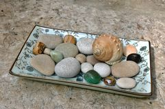 Seashell, pebbles and gemstones on the plate. Little treasures from beach decorated on the plate Royalty Free Stock Photography
