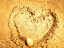 Seashell on the sand. Drawing heart on the sand Royalty Free Stock Image