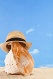 Seashell with straw hat Stock Photo