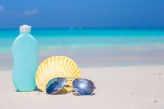 Seashell, sunglasses and suncream on white sand Royalty Free Stock Photo
