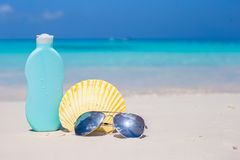 Seashell, sunglasses and suncream on white sand Royalty Free Stock Images