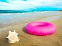 Seashell and tube. Seashell and inflatable tube on the beach Stock Photo