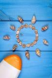 Seashells в форме солнца и лосьона солнца на голубых досках, аксессуарах на лето Стоковое Изображение